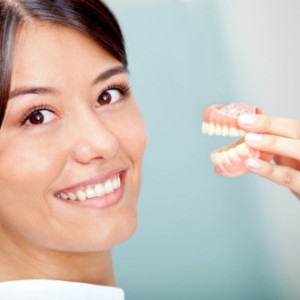 Woman holding a teeth sample or prosthesis at the dentist